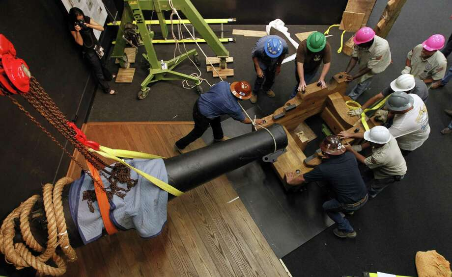 Workers with Domac Inc. and the City of Texas City slide the Marsilly Gun Carriage under the Dahlgren gun as they position the Civil War cannon in its new exhibit at the Texas City Museum on Wednesday June 18, 2014, in Texas City, Texas.  A Civil War cannon from the 1863 sinking of the USS Westfield has a new resting place at a Texas museum just miles from where the ship went down.   Officials at the Texas City Museum on Wednesday welcomed the restored 12-foot cannon for a maritime exhibit. (AP Photo/The Galveston County Daily News, Jennifer Reynolds) MANDATORY CREDIT; MAGS OUT; TV OUT Photo: Jennifer Reynolds, MBR / Associated Press / The Galveston County Daily News