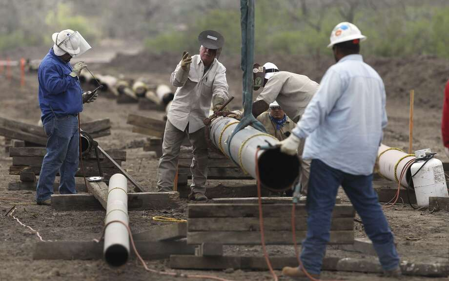 Welding crews work on an oil and gas pipeline east of Karnes City. A 730-mile crude oil and condensate pipeline is in the works from West Texas to Corpus Christi. When completed, it would be able to transport 440,000 barrels a day from West Texas alone. Photo: San Antonio Express-News /File Photo / Midland