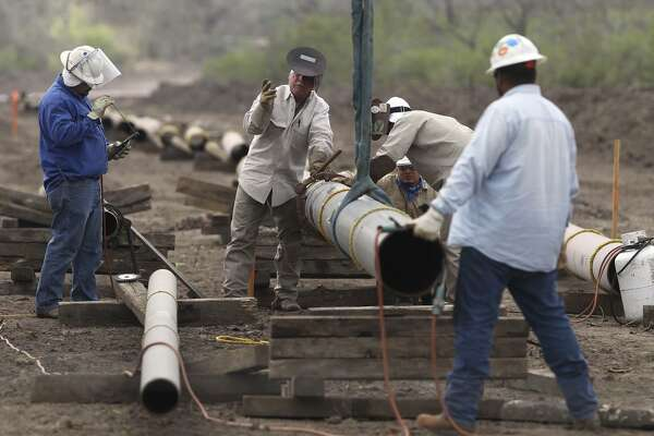 Welding crews work on an oil and gas pipeline east of Karnes City. A 730-mile crude oil and condensate pipeline is in the works from West Texas to Corpus Christi. When completed, it would be able to transport 440,000 barrels a day from West Texas alone.