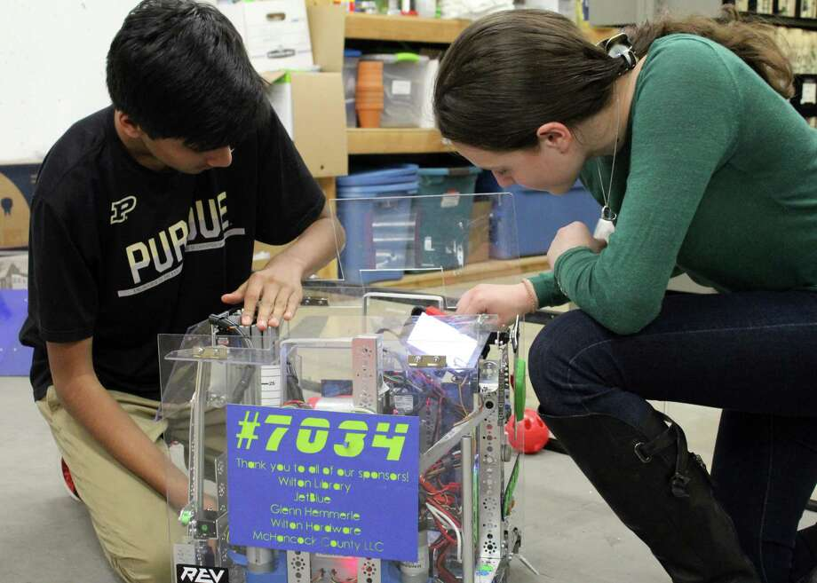 Rohit Singhal and Nikia Muraskin of Wilton Library's robotics team, Singularity Technology, inspecting the team's robot. Photo: Stephanie Kim / Hearst Connecticut Media