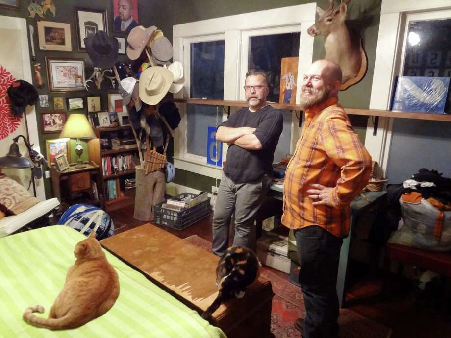 Rick Frederick and Chris Sauter, with cat Chuckie (named for the late SA aritst Churck Ramirez) on the bed, talk about the decor of their bedroom. Photo: Steve Bennett / San Antonio Express-News