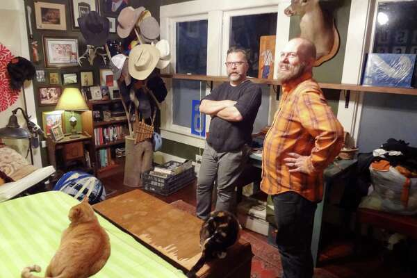 Rick Frederick and Chris Sauter, with cat Chuckie (named for the late SA aritst Churck Ramirez) on the bed, talk about the decor of their bedroom.