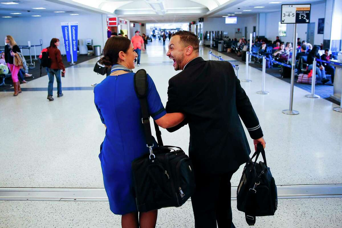 United Airlines flight attendant trainees Lauren Franco, left, and Nicholas Villeneuve laugh in terminal at George Bush Intercontinental Airport after completing their two training flights before gradating flight attendant school and getting their wings Monday, Nov. 7, 2016. ( Michael Ciaglo / Houston Chronicle )