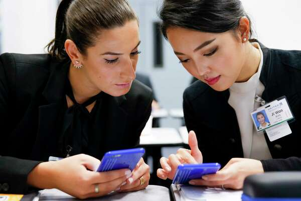 United Airlines flight attendant trainees Lauren Franco, left, and Ji Won Kim, right, study the layout of an airplane on their phones Friday, Nov. 4, 2016 in Houston. ( Michael Ciaglo / Houston Chronicle )