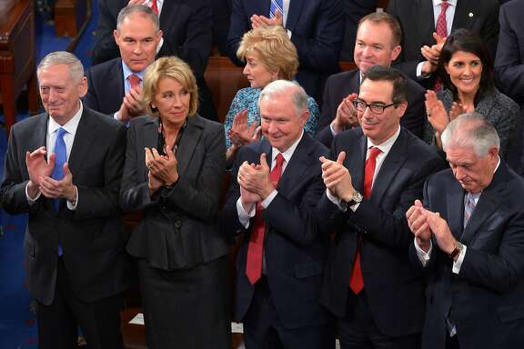 """(FILES) This February 28, 2017 file photo shows Attorney General Jeff Sessions (C) with cabinet members (from left) Defense Secretary James Mattis, Education Secretary Bettsey Devos, Sessions, Treasury Secretary Steven Mnuchin, and Secretary of State Rex Tillerson, applauding US President Donald Trump during his address to a joint session of Congress at the US Capitol in Washington, DC. US Attorney General Jeff Sessions said March 2, 2017 he will recuse himself """"whenever it's appropriate"""" from Justice Department probes into alleged ties between Donald Trump's campaign and the Russian government, after coming under fire himself for contacts with Moscow. Sessions met twice with Russia's ambassador to Washington last year, the White House confirmed, while he was serving as both a senator and a top foreign policy adviser to Trump's campaign. / AFP PHOTO / MANDEL NGANMANDEL NGAN/AFP/Getty Images"""