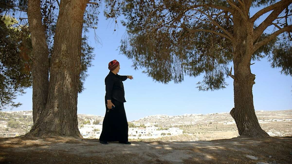 """An unnamed Palestinian woman points toward settlers' enroachments in """"The Settlers."""""""