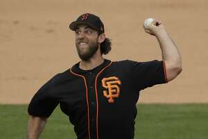 San Francisco Giants starting pitcher Madison Bumgarner throws during the second inning of a spring training baseball game against the San Diego Padres Tuesday, Feb. 28, 2017, in Peoria, Ariz. (AP Photo/Charlie Riedel)