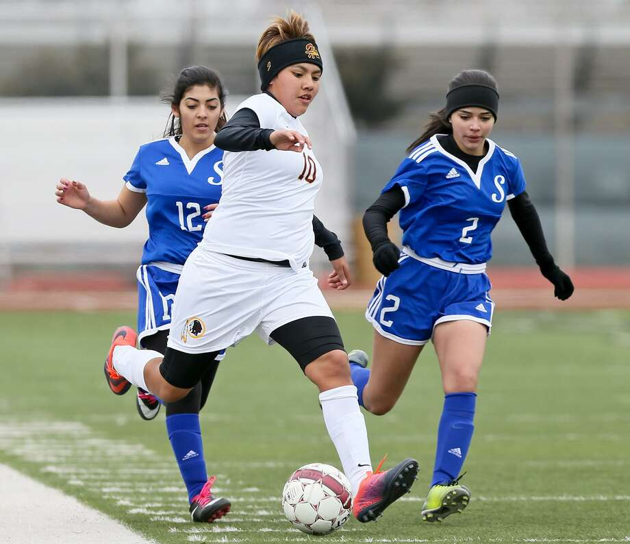 Harlandale's Jazmine Baltazar (center) drives the ball past Somerset's Larissa Galvez (left) and Valeria Munoa during their opening game in the Harlandale ISD Varsity Girls Soccer Showcase Tournament at Harlandale Memorial Stadium on Friday, Jan. 6, 2017.  Baltazar scored four goals to lead the Lady Indians past Somerset 9-0.  MARVIN PFEIFFER/ mpfeiffer@express-news.net Photo: Marvin Pfeiffer, Staff / San Antonio Express-News / Express-News 2016