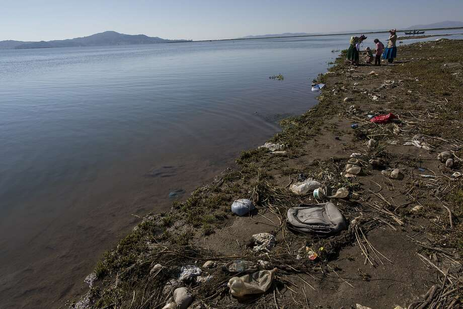 Trash covers the shores of Lake Titicaca as environmental activist Maruja Inquilla talks to residents in the village of Coata, in the Puno region about dangers to their food and water. Photo: Rodrigo Abd, Associated Press