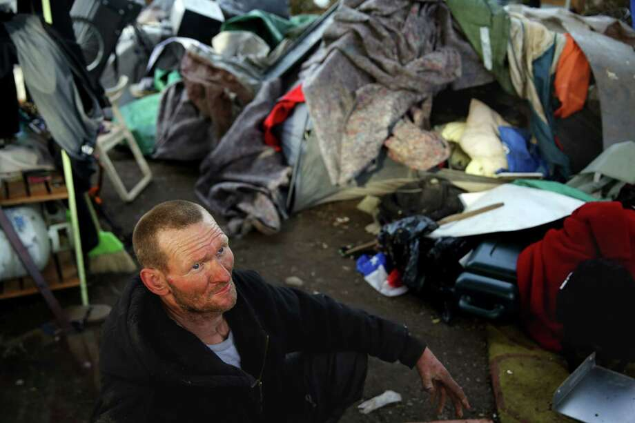 Teman cleans up around a tent encampment where he lives with five or six others under the south end of the Ballard Bridge, Wednesday, March, 1, 2017. City officials announced plans to sweep the camp this week. Photo: GENNA MARTIN, SEATTLEPI.COM / SEATTLEPI.COM