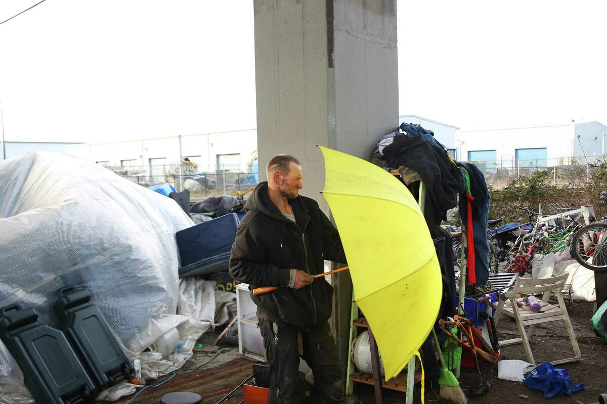 Teman tosses finds an umbrella as he cleans up around a tent encampment where he lives with five or six others under the south end of the Ballard Bridge, Wednesday, March, 1, 2017.