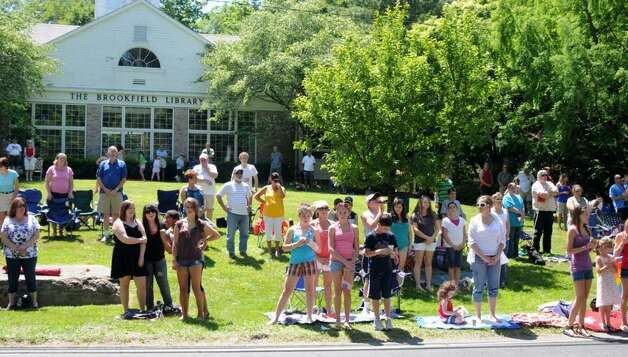 Parade goers stand in front of the brookfield library for West brookfield elementary school craft fair