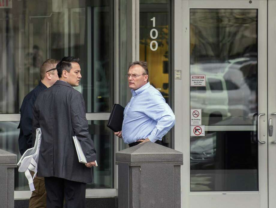 Steve Settingsgaard (right), head of North American security for Caterpillar, stands outside of the company's world headquarters Thursday in Peoria, Ill., talking with two law enforcement officials. Federal law enforcement officials Thursday executed a search warrant at Caterpillar's Peoria headquarters and a facility that ships parts overseas. Photo: David Zalaznik /Associated Press / Journal Star