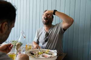 Justin Champaign shoots an oyster at the small neighborhood restaurant Red Hill Station in San Francisco, Calif., Sunday, August 24, 2014.