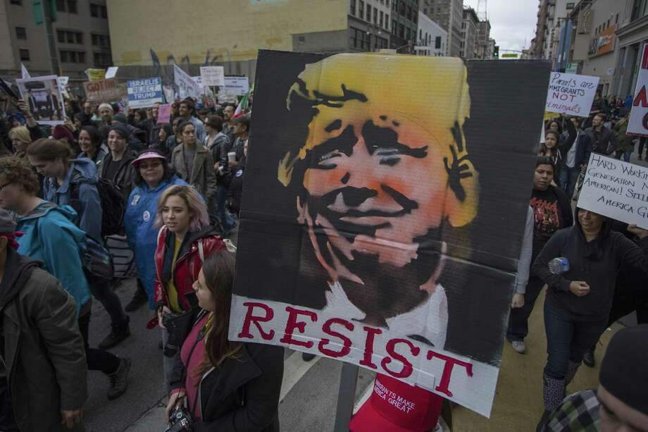 People carry signs during the Immigrants Make America Great March to protest actions being taken by the Trump administration on Feb. 18 in Los Angeles, California. President Trump's new policies are causing fear and unrest in immigrant communities. Photo: David McNew /Getty Images / 2017 Getty Images