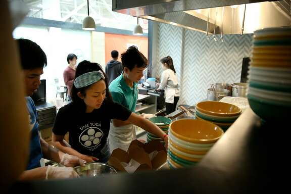 Nite Yun (wearing a bandana) and her employees prepare food orders at Nyum Bai on Thursday, March 2, 2017, in Emeryville, Calif. Yun, the owner, was aided by La Cocina, a kitchen incubator that helps women of color and immigrants by providing affordable kitchen space.