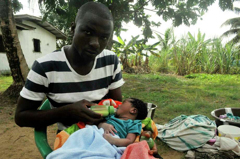 James Harris, feeding his child outside his house in Monrovia, Liberia, said nurses were too afraid to touch his wife, Salome Karwah, even though she was immune to the Ebola virus. Photo: Abbas Dulleh, STR / Copyright 2017 The Associated Press. All rights reserved.