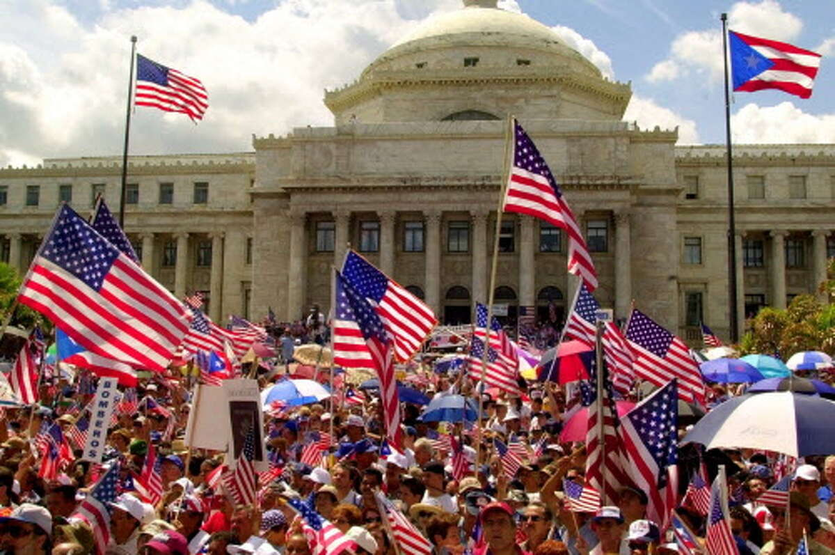 Thousands waves American flags during a rally celebrating U.S. Citizenship at the Capitol in San Juan, Puerto Rico Sunday, March 5, 2000. Puerto Ricans were granted U.S. citizenship by President Woodrow Wilson in 1917 through the Jones Act.