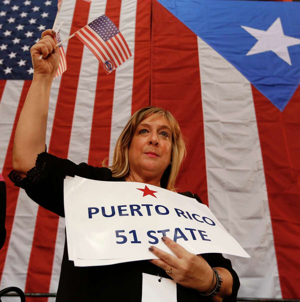 Audience member Arlene Dudeil waves flags during a Republican presidential candidate, Sen. Marco Rubio, R-Fla., rally in Toa Baja, Puerto Rico, Saturday, March 5, 2016.