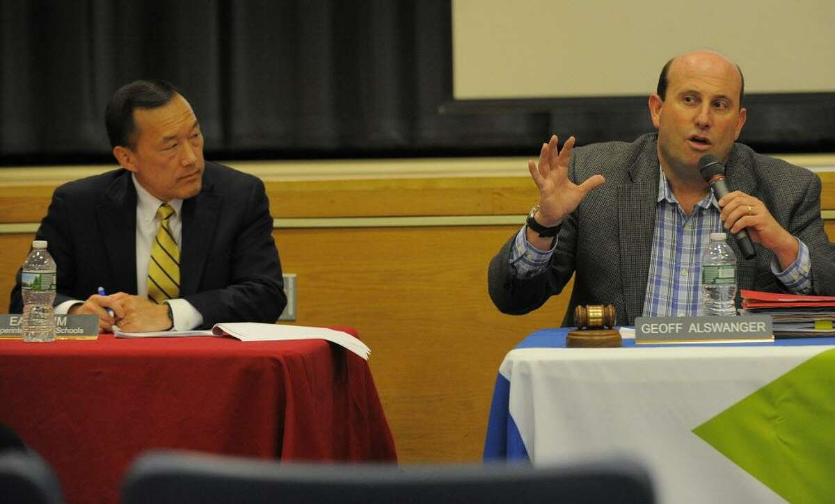 FILE - Board member Geoff Alswanger, right, welcomes Superintendent Earl Kim to present his proposed budget to members of the Stamford Schools Board of Education during a public hearing at Westover Magnet Elementary School in Stamford on Feb. 7, 2017.