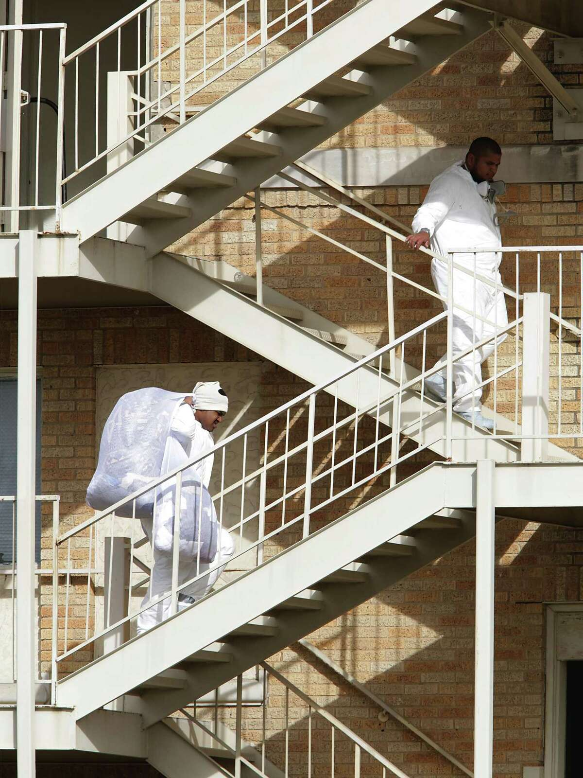 Workers dressed in white protective suits carry bags of linens and clothing, cleaned for bedbugs, back up to a fumigated floor of the Aurora Apartments on March 2, 2017. The historic apartment building is being fumigated for infestations of roaches and bed bugs.