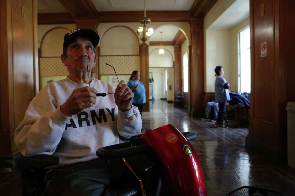 Cirilio Garay, 75, a resident of Aurora Apartments, sits in the building's lobby with other residents while fumigation is under way for infestations of roaches and bed bugs in San Antonio on March 2. Garay's apartment will be treated Saturday.