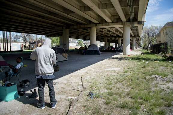 "A man who gave his name as, ""Mr. Wheeler Station,"" checks his belongings at his campsite under U.S. 59 near downtown Houston Thursday, March 2, 2017. (Jon Shapley / Houston Chronicle)"
