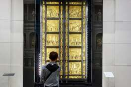 """A visitor admires Lorenzo Ghiberti's """"Gates of Paradise"""" in Florence's newly refurbished Duomo Museum."""