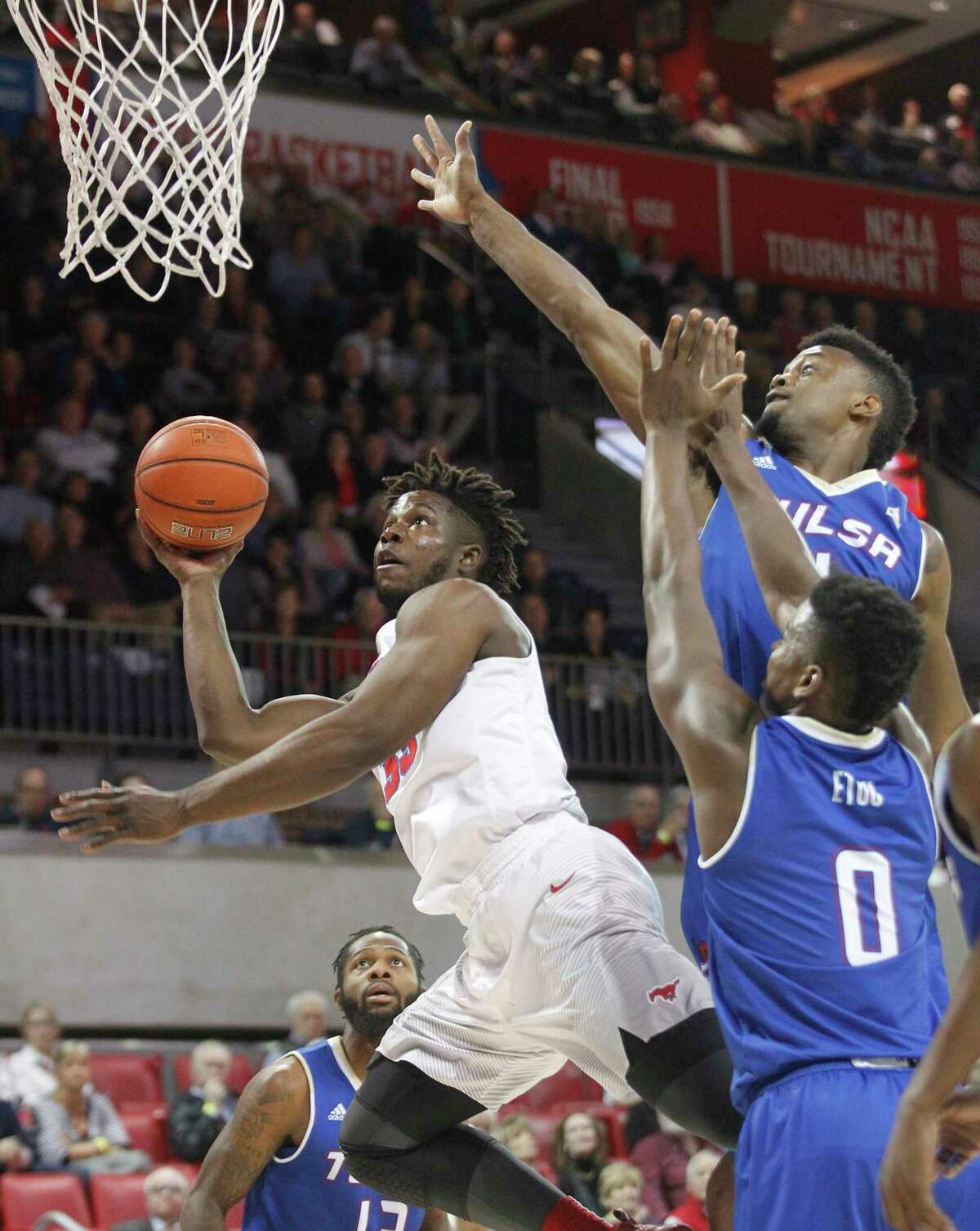 SMU forward Semi Ojeleye, left, puts up a shot while being pressured by Tulsa forwards Martins Igbanu (1) and Junior Etou (0) during the first half of an NCAA college basketball game, Thursday, March 2, 2017, in Dallas.