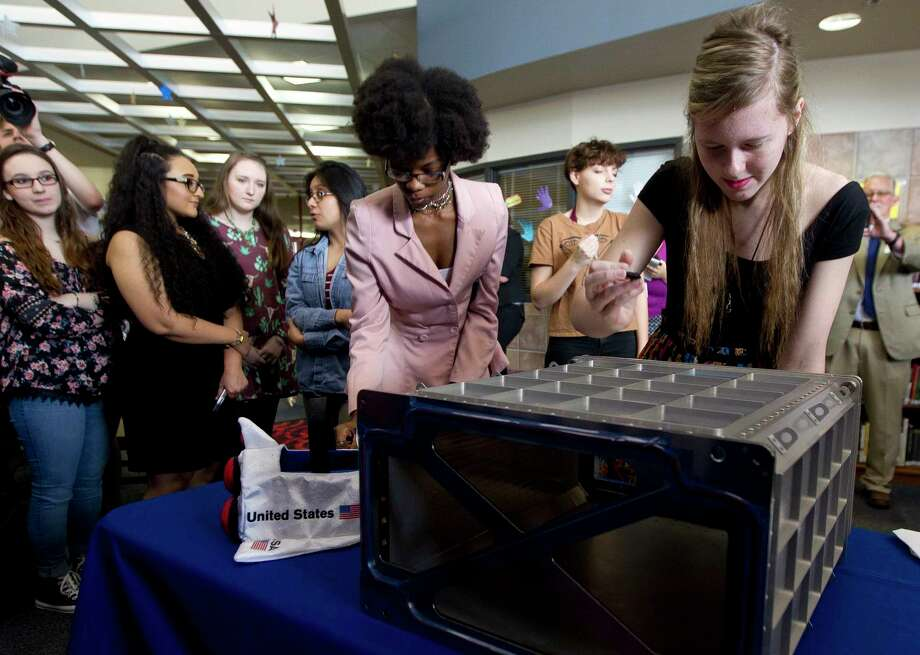 Grace Forney signs a locker to be used on the International Space Station at Oak Ridge High School Thursday in Conroe. Students from the school's advanced fashion design class sewed eight equipment covers and two privacy curtains for the permanent multipurpose module in the International Space Station. The students' work will be put to use this summer when the Orbital 7, a cargo resupply mission, is launched. Photo: Jason Fochtman, Staff Photographer / © 2017 Houston Chronicle