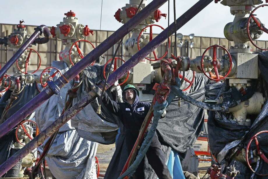 An energy worker adjusts pipes during a hydraulic fracturing operation near Mead, Colo.  Photo: Brennan Linsley, STF / AP