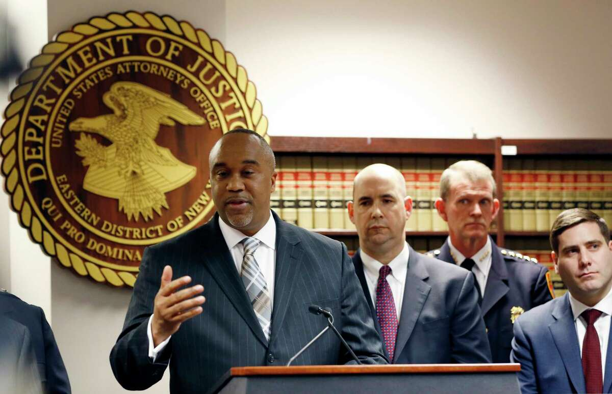 Robert Capers, left, U.S. Attorney for the Eastern District of New York, speaks during a press conference, Thursday, March 2, 2017, in Central Islip, N.Y., to announce that 13 MS-13 gang members were indicted in the killings last year of three teenagers on Long Island. The victims include two high school girls found dead last September. William Sweeney, FBI assistant director in charge of the New York FBI, second from left, and Sufflok County police commissioner Timothy Sini, far right, listen as Capers speaks. (AP Photo/Kathy Willens) ORG XMIT: NYKW101