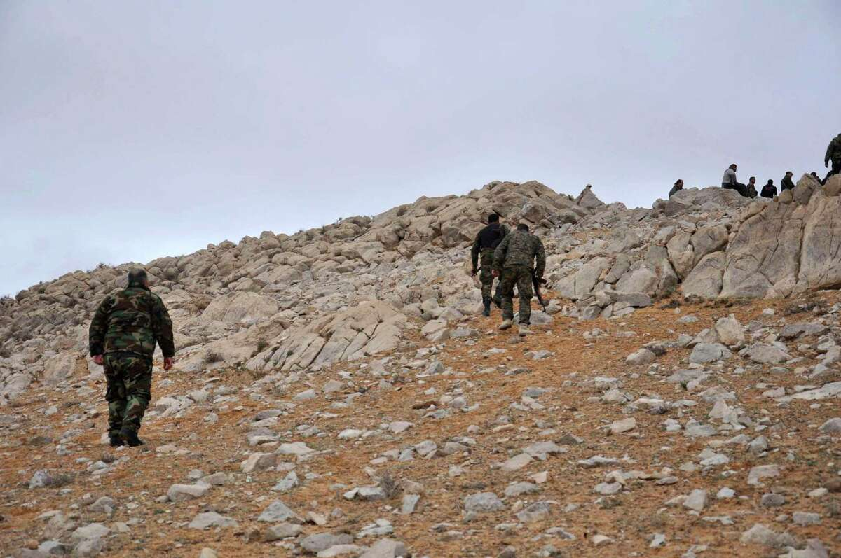 In this photo released by the Syrian official news agency SANA, Syrian forces take up positions during fighting between Government forces and Islamic State group militants in the ancient city of Palmyra, near Homs, Syria, Thursday, March 2, 2017. Syrian state media says government forces have reached the edge of Palmyra and are poised to reclaim the historic town from the Islamic State group. (SANA via AP) ORG XMIT: HAS105