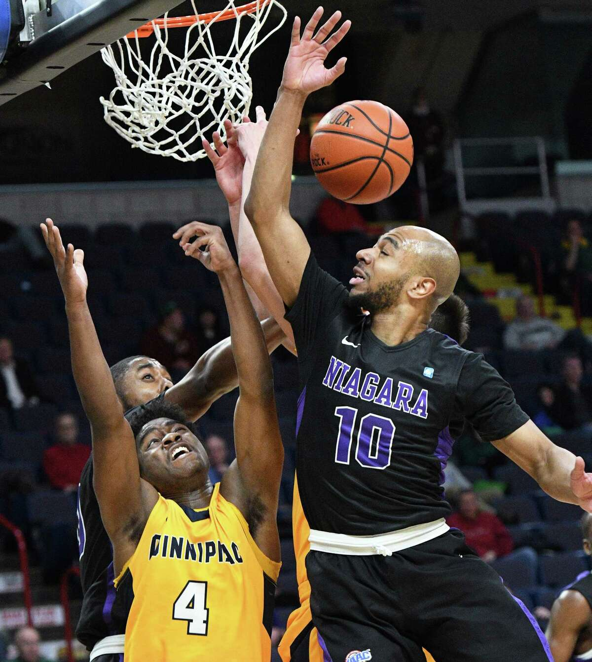 Quinnipiac's #4 Phil Winston battles Niagara's #20 Maurice Taylor Jr., left, and #10 Kahlil Dukes for a rebound during their first round MACC tourney game at the Times Union Center Thursday March 2, 2017 in Albany, NY. (John Carl D'Annibale / Times Union)
