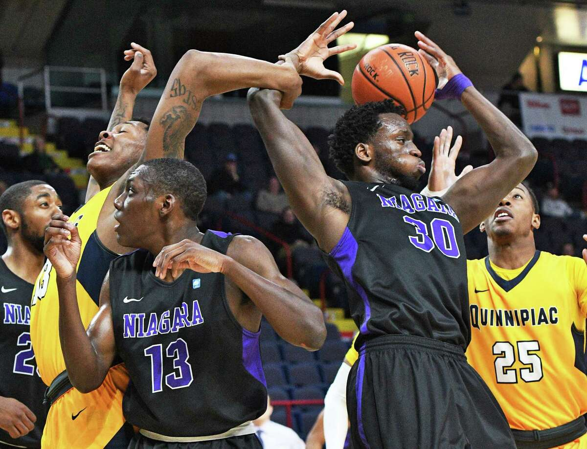 Niagara's #13 Matt Scott and #30 Ali Tew battle Quinnipiac's #13 Chaise Daniels, left, and #25 Ja'Kwan Jones, right, for a rebound during their first round MACC tourney game at the Times Union Center Thursday March 2, 2017 in Albany, NY. (John Carl D'Annibale / Times Union)