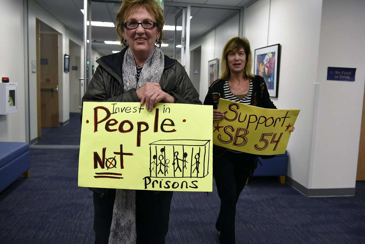 Peggy Kroll, left, and Connie Chiba hold signs following a joint town hall meeting held by Senator Steve Glazer, D-Orinda, and Assemblywoman Catharine Baker, R-San Ramon, at City Hall in San Ramon, CA, on Thursday March 2, 2017.