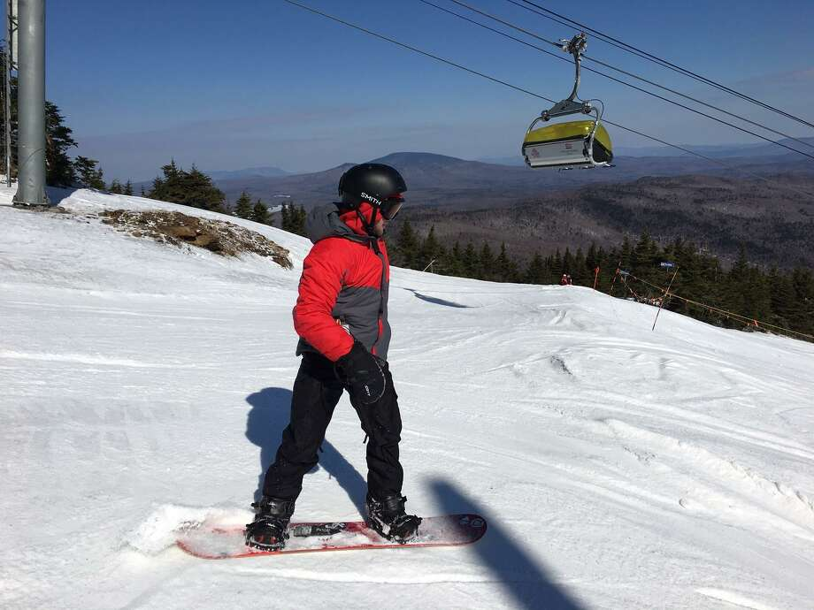 A snowboarder prepares to take a ride down from Mount Snow's summit on Monday, Feb. 27, 2017. The southern Vermont resort is selling $17 lift tickets for St. Patrick's Day. It's one of the many deals out there for end of the season skiing and snowboarding. Photo: Jim Shay /Hearst Connecticut Media