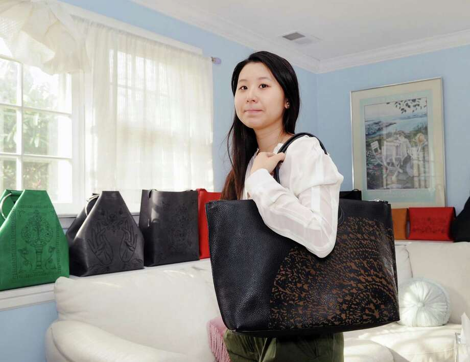 Aerim Kim, creative director for Theikona, with one of the leather bags that she along with her sister Lindsey Kim designed at her company's office in the Riverside section of Greenwich, Conn., Tuesday, Feb. 28, 2017. The Kim sisters, graduates of Greenwich High School and the Parsons Fashion School of Design, are co-founders of the luxury leather goods company. Aerim Kim said the company's products are made by artisans in America. The company has an online presence at: http://www.theikona.com. Photo: Bob Luckey Jr. / Hearst Connecticut Media / Greenwich Time