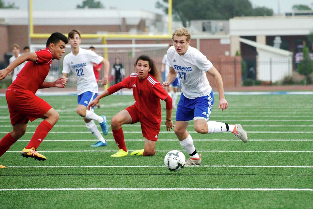 Friendswood's A.J. Buchman (17) looks to move the ball upfield against Goose Creek Memorial's Gabriell Ibarra (3) last week in the Friendswood Soccer Invitational.