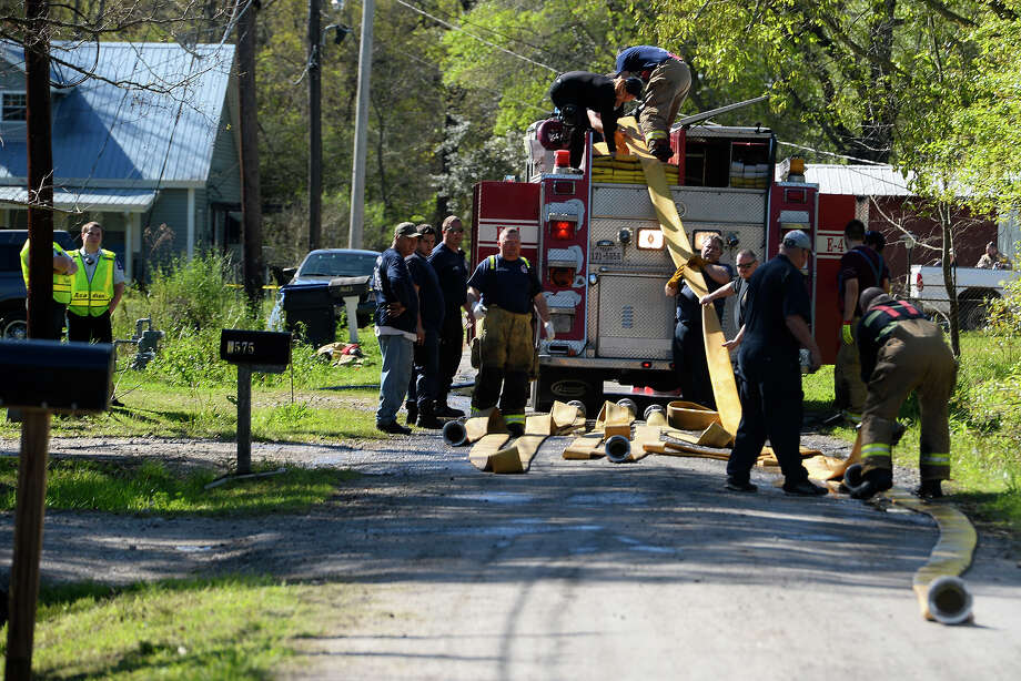 Firefighters pack up their hoses at a house fire on Dronett Street in Orangefield on Friday morning. An unidentified white male died in the fire, according to Janois Straus with the Orange County Sheriff's Office.  Photo taken Friday 3/3/17 Ryan Pelham/The Enterprise Photo: Ryan Pelham, Ryan Pelham/The Enterprise / ©2017 The Beaumont Enterprise/Ryan Pelham