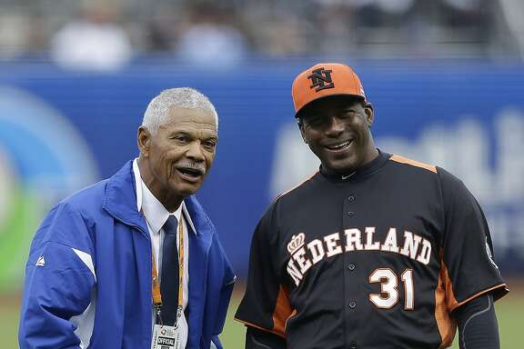 Former baseball player Felipe Alou, left, and the Netherlands' manager Hensley Meulens prepare to throw out the ceremonial first pitch before a semifinal game of the World Baseball Classic between the Netherlands and the Dominican Republic in San Francisco, Monday, March 18, 2013. (AP Photo/Jeff Chiu, Pool)
