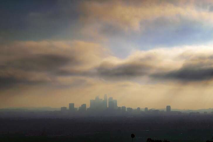 FILE - In this Aug. 12, 2016 file photo, downtown Los Angeles is shrouded in early morning coastal fog. A long-term plan for cleaning up the air in a huge swath of smoggy Southern California is due for consideration by regulators. Directors of the South Coast Air Quality Management District are expected to vote on the plan Friday, March 3, 2017. (AP Photo/Richard Vogel, File)