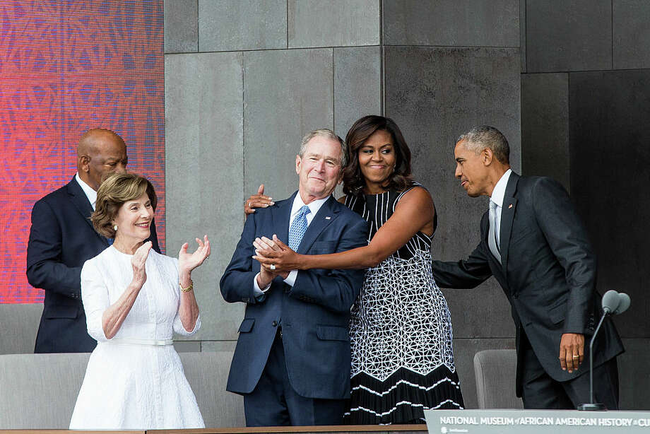 Former US President George W. Bush and former First Lady Michelle Obama embrace at the opening ceremony for the Smithsonian National Museum of African American History and Culture.Turns out George and Michelle are good friends. Keep clicking for a look at some of Bush's favorite paintings.