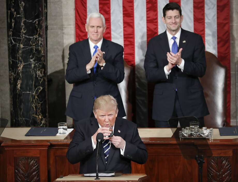 President Trump pauses to take a sip of water during his address to a joint session of Congress on Tuesday as Vice President Mike Pence (left) and House Speaker Paul Ryan, R-Wis., applaud. Photo: Pablo Martinez Monsivais, Associated Press