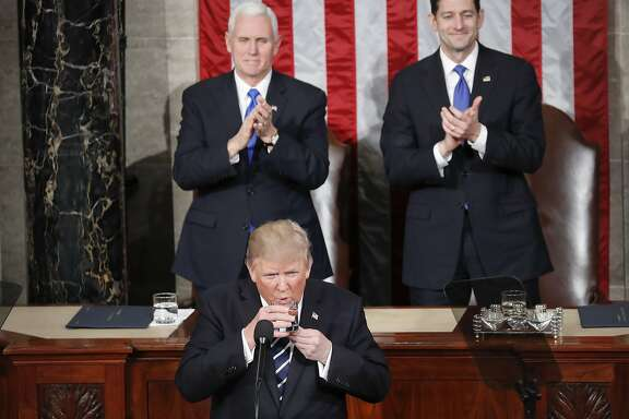 President Donald Trump takes a sip of water from his glass during his address to a joint session of Congress on Capitol Hill in Washington, Tuesday, Feb. 28, 2017. Standing up and applauding in the back are Vice President Mike Pence and House Speaker Paul Ryan of Wis. (AP Photo/Pablo Martinez Monsivais)