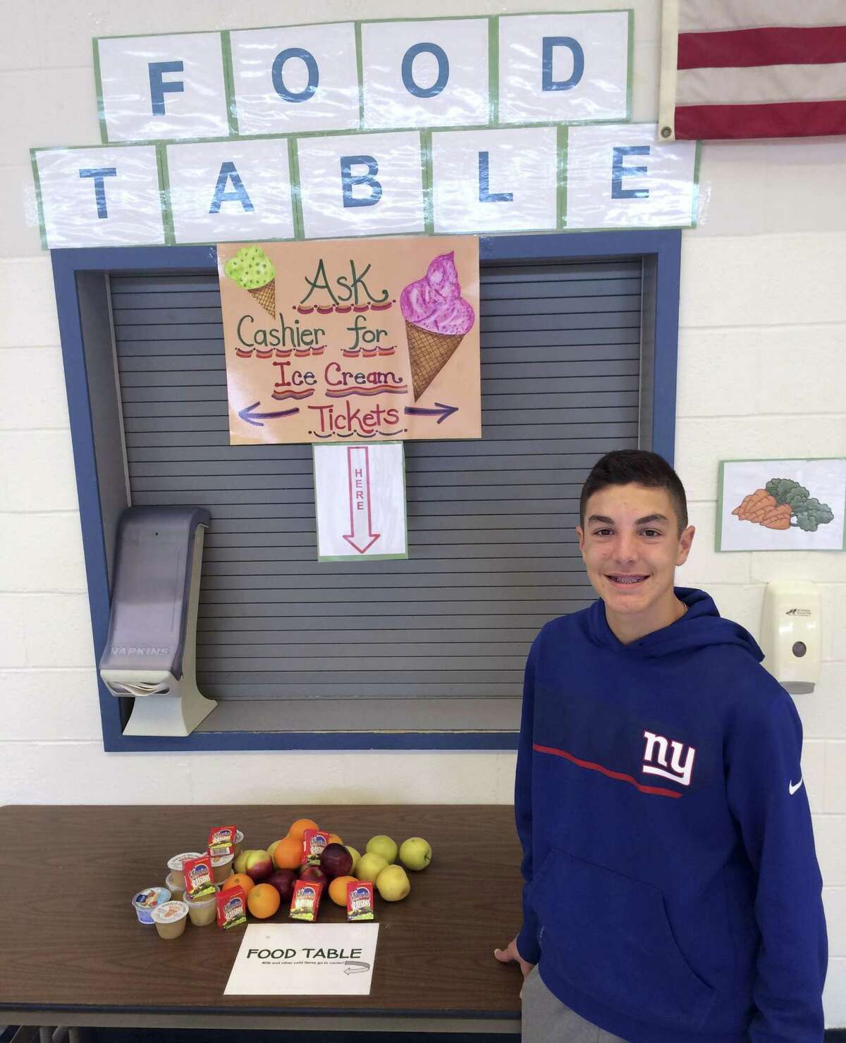 In this Tuesday, Feb. 28, 2017 photo, Nick Iannone, 14, poses in front of the share table he launched as a school project at James H. Moran Middle School in Wallingford, Conn. School officials there are criticizing a state policy change that restricts sharing of some uneaten food items. (AP Photo/Michael Melia)