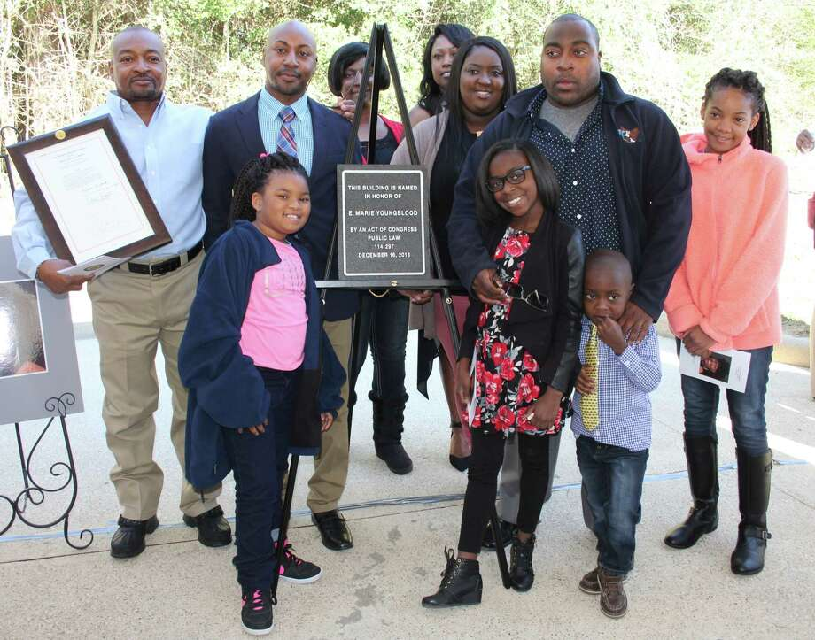 The family of E. Marie Youngblood stands alongside the plaque that will be placed in the Coldspring post office lobby in the coming weeks. The post office was officially renamed in Youngblood's memory on Friday. The postal carrier was murdered in May 2013 while delivering mail in a rural area of Coldspring. Photo: Vanesa Brashier