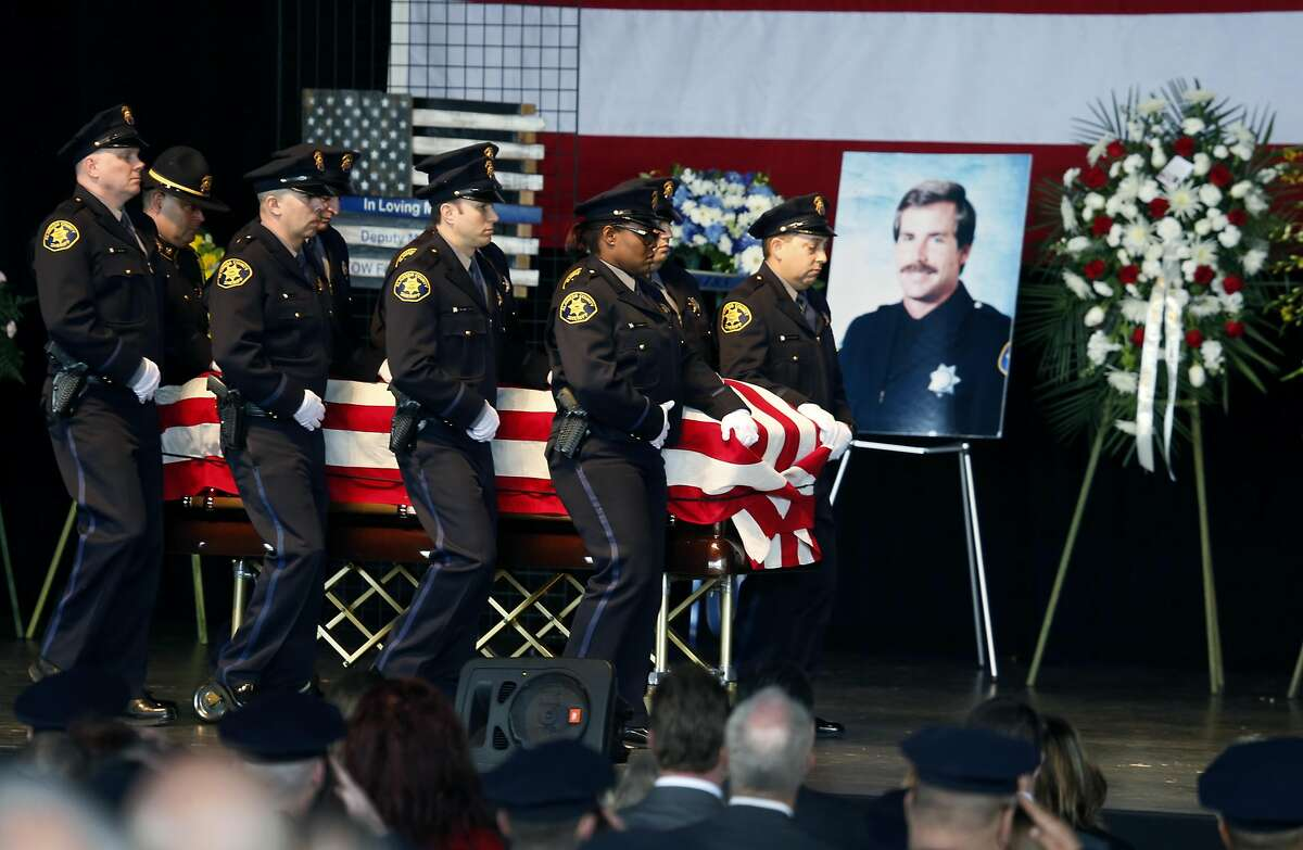 Pallbearers carry Alameda County sheriff's deputy Mike Foley's casket onto the stage for a funeral service at the Concord Pavilion in Concord, Calif. on Friday, March 3, 2017. Foley died from injuries sustained when he was accidentally struck by a sheriff's department bus at the county jail last month.