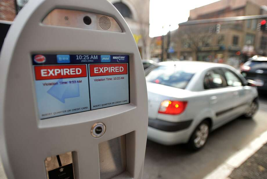 A woman receives a ticket after overstaying the five minute grace period on her automated parking meter on Main Street in Bridgeport, Conn. on Tuesday, February 28, 2017. Photo: Brian A. Pounds / Hearst Connecticut Media / Connecticut Post