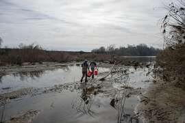 Department of Water Resources contract biologist, Alana Imrie, left, and Kevin Moncrief, scientific aide with the California Department of Fish and Wildlife, prepare to count and measure fish during a project where staff and contractors with the California Department of Fish and Wildlife and the California Department of Water Resources rescue fish trapped in small pool near the Feather River in Gridley, Calif on Friday, March 3, 2017.